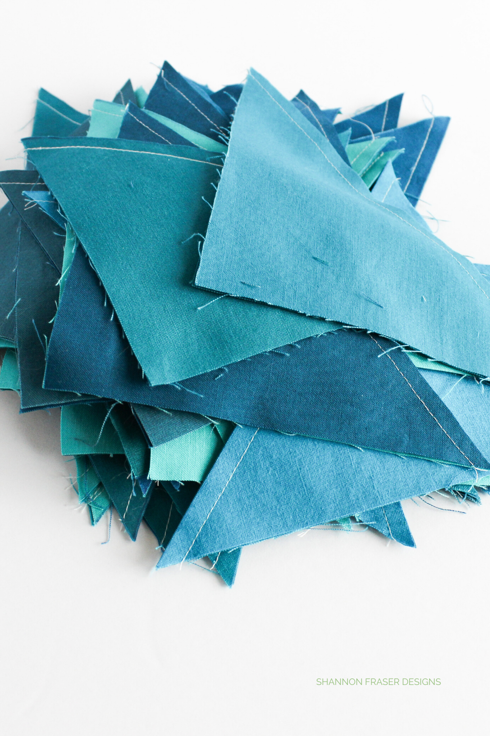 All different shades of blue half square triangles ready to be pressed and trimmed