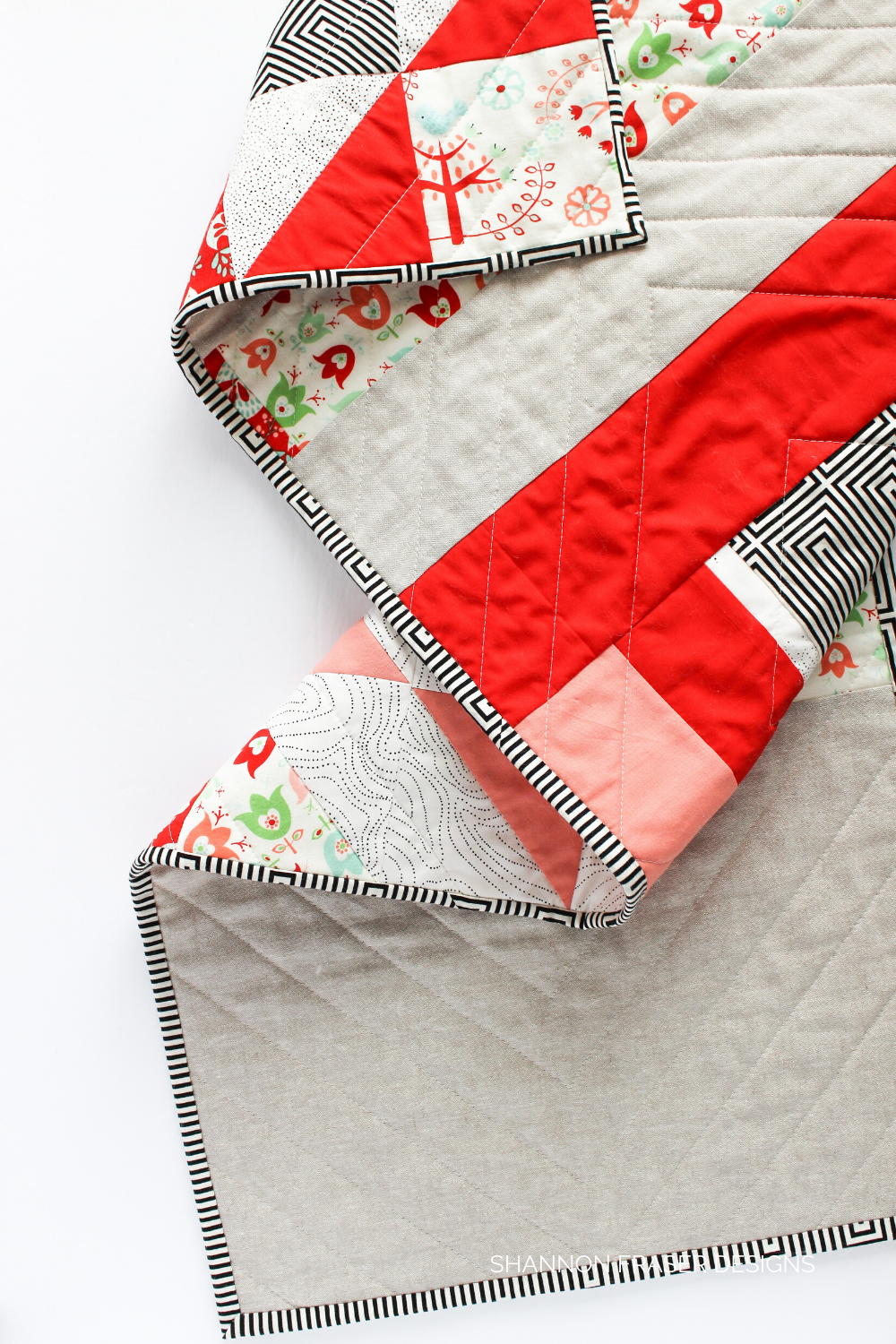 Holiday Modern Aztec quilted table runner folded on the table | Christmas quilting project | Shannon Fraser Designs #tablelinen
