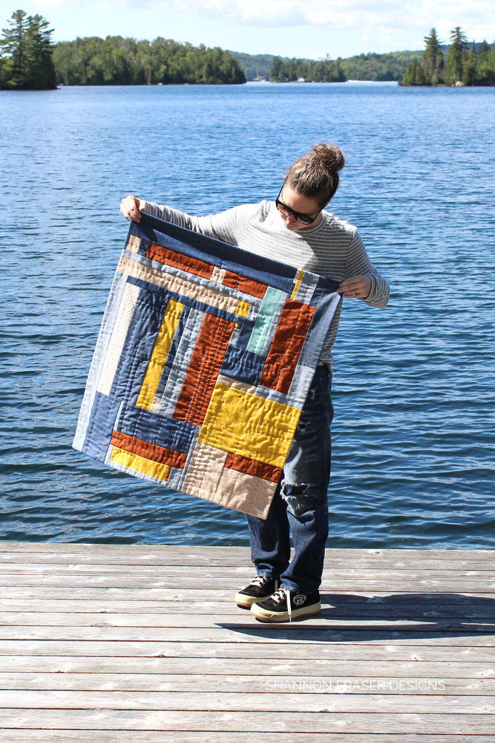 Shannon holding the Improv Landmark quilted wall hanging at the end of a dock! This one was made from scraps and then hand quilted for all the quilty texture and detail | Shannon Fraser Designs #modernquilter