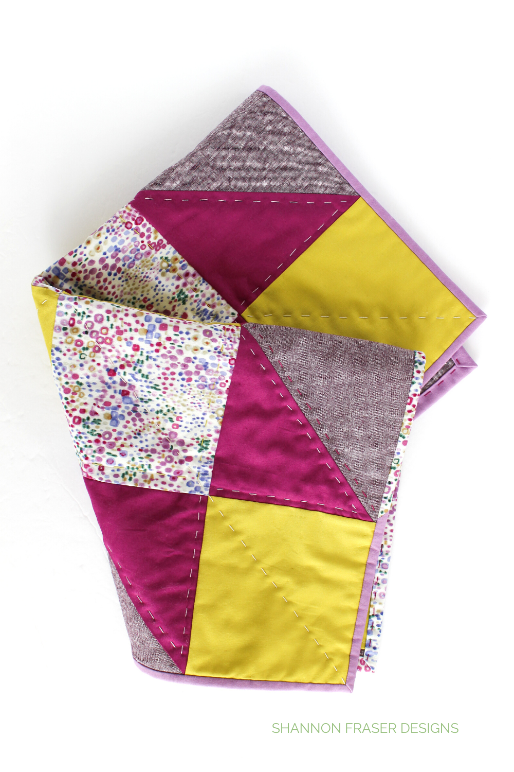 Purple, wasabi, eggplant and floral Indian Star quilted mini wall hanging folded in half | Quilt Big Book Tour | Shannon Fraser Designs #quiltedwallhanging