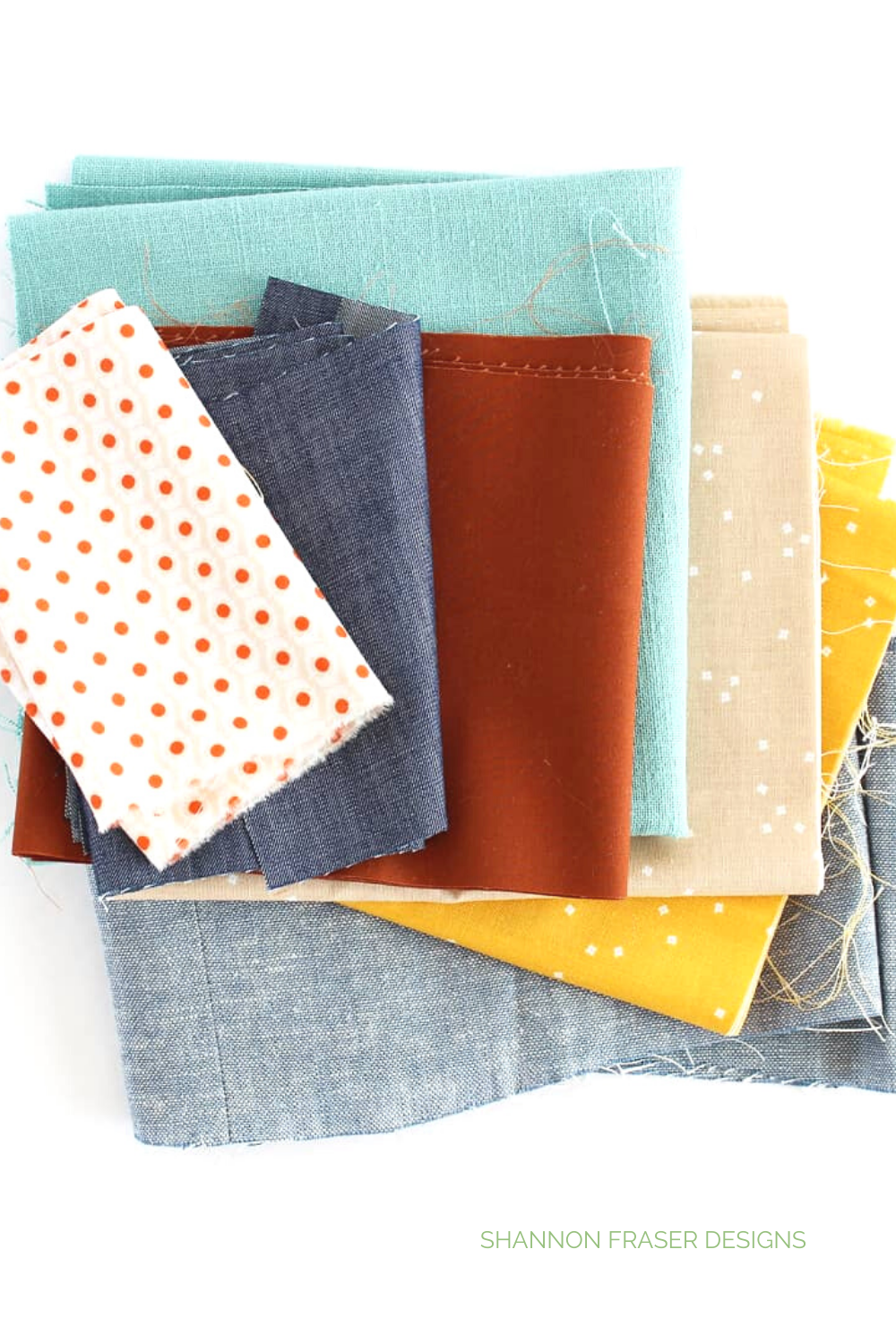 Stack of fabrics featured in the hand quilted Landmark wall hanging I made from the Urban Quilting book | Shannon Fraser Designs #fabricpull