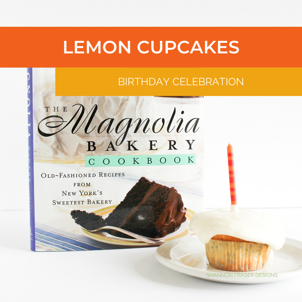 Lemon cupcake with candle in front of Magnolia Bakery cookbook