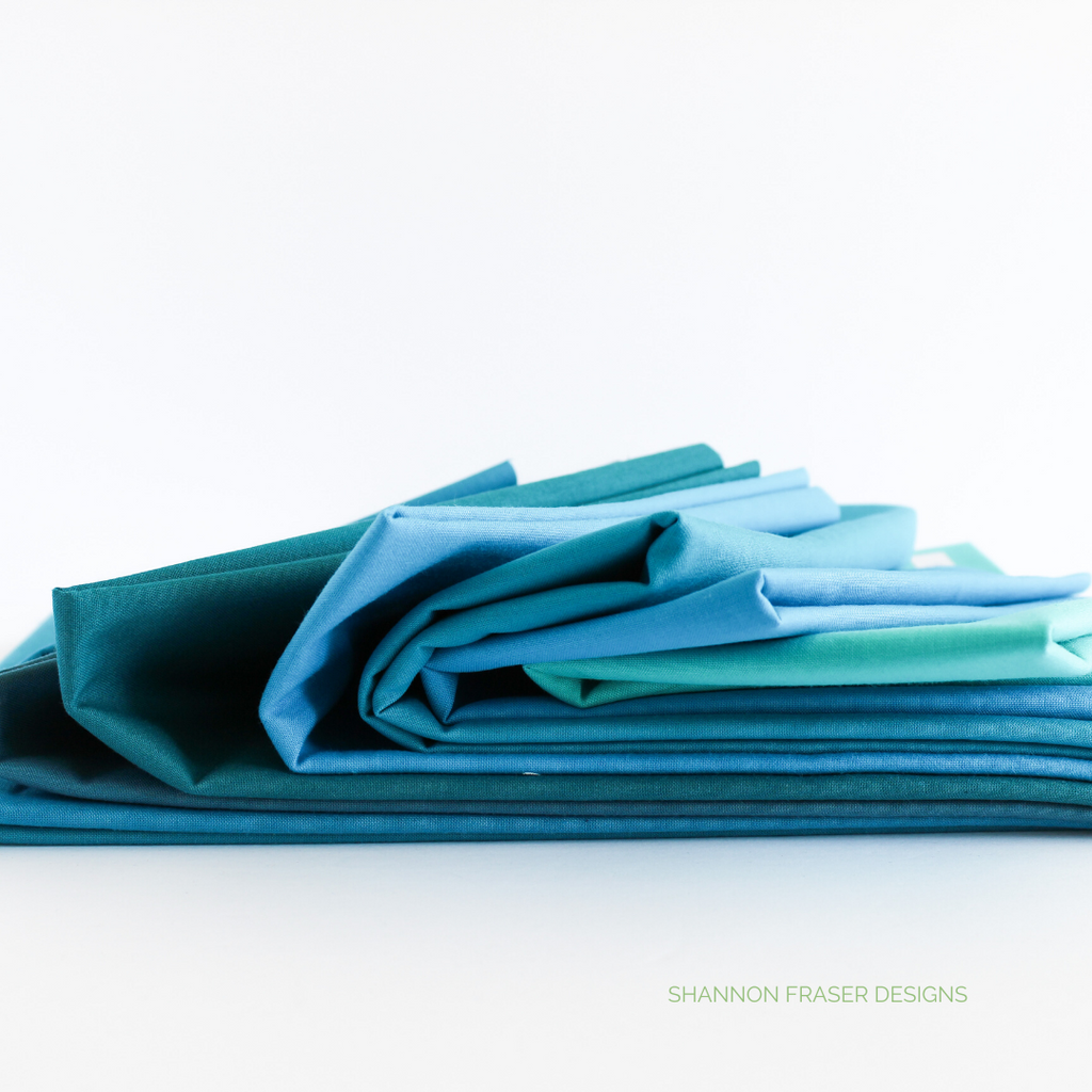 Stack of Kona Cotton in various shades of blues and turquoise