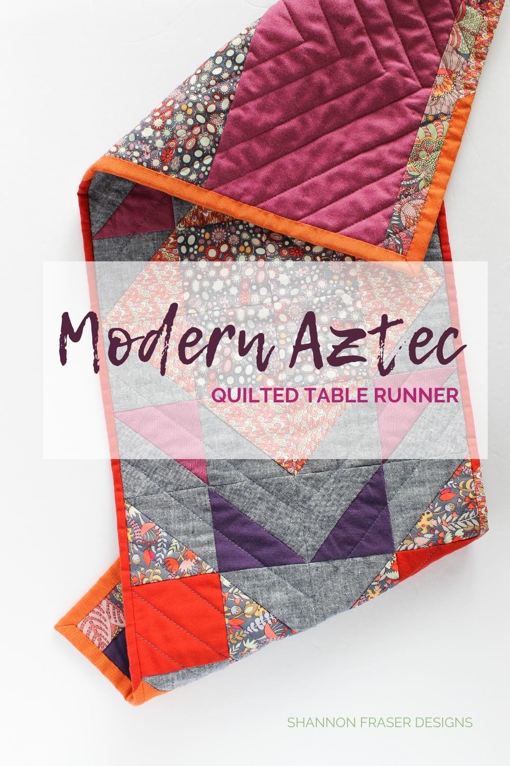 Modern Aztec quilted table runner folded on the table - red, orange, purple, navy and floral table runner | Fall home decor | Shannon Fraser Designs #tablerunner