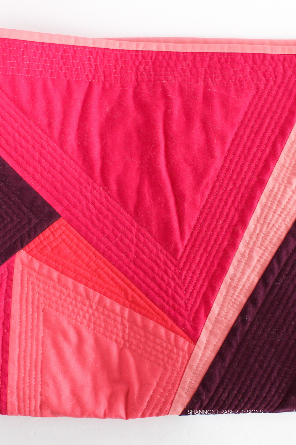 Machine quilting details using 50wt aurifil thread to echo each triangle featured in the One Hundred and Eighty Degree quilted wall hanging. A creative challenge with the MtlMQG inspired by the work of artist Guido Molinari | quilt and design by Shannon Fraser Designs #quilt #quilting #machinequilted
