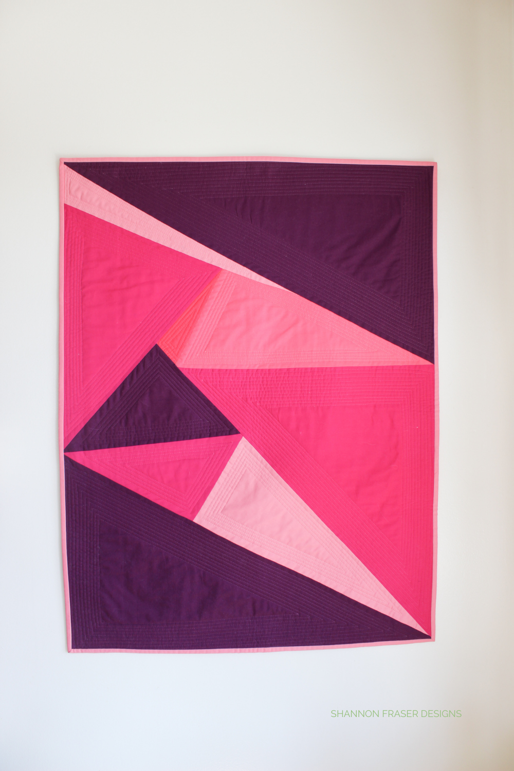 One Hundred and Eighty Degrees Quilt hanging on the wall | Shannon Fraser Designs #sewsolids #solidsquilt #modernwallart