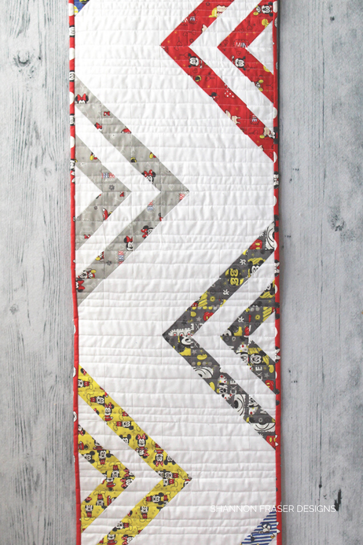 Peaks and Valleys quilted table runner featuring Mickey & Friends fabric laid out against a gray wood grain background
