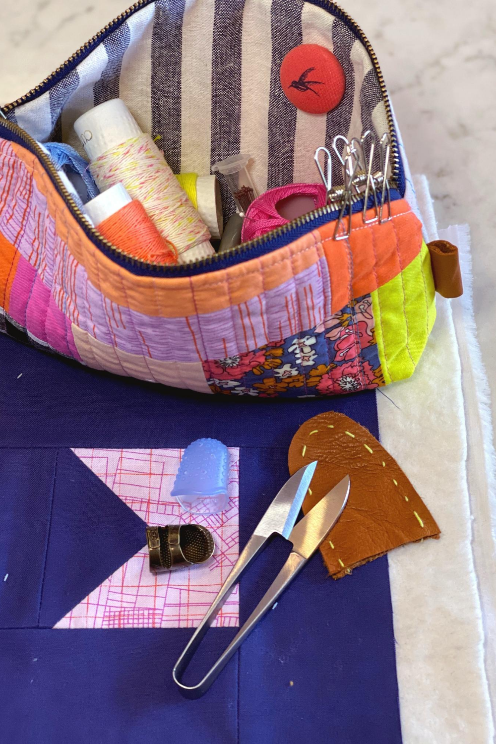 Flip's scrappy pink Petal Pouch zipped open to access her fav sewing notions for hang quilting | What's in Your Sewing Bag? Special guest: Flip & Co | Shannon Fraser Designs #handquilting