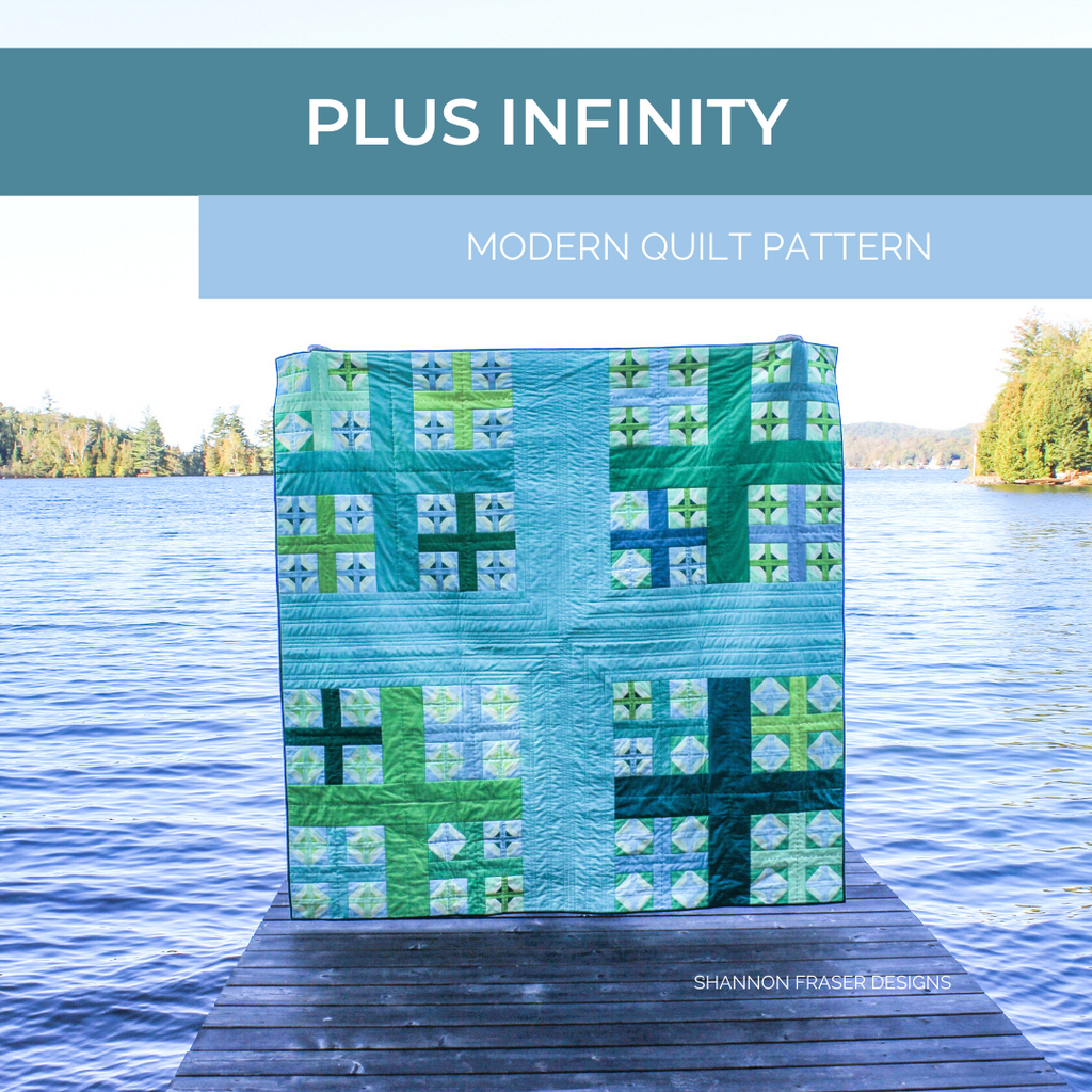 Plus Infinity quilt in blues and greens on the dock in front of a lake in the summer time | Shannon Fraser Designs
