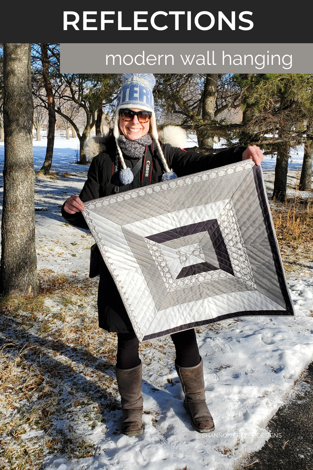 Shannon out in the winter wild holding up her completed Reflections quilted wall hanging  #quiltsinthewild