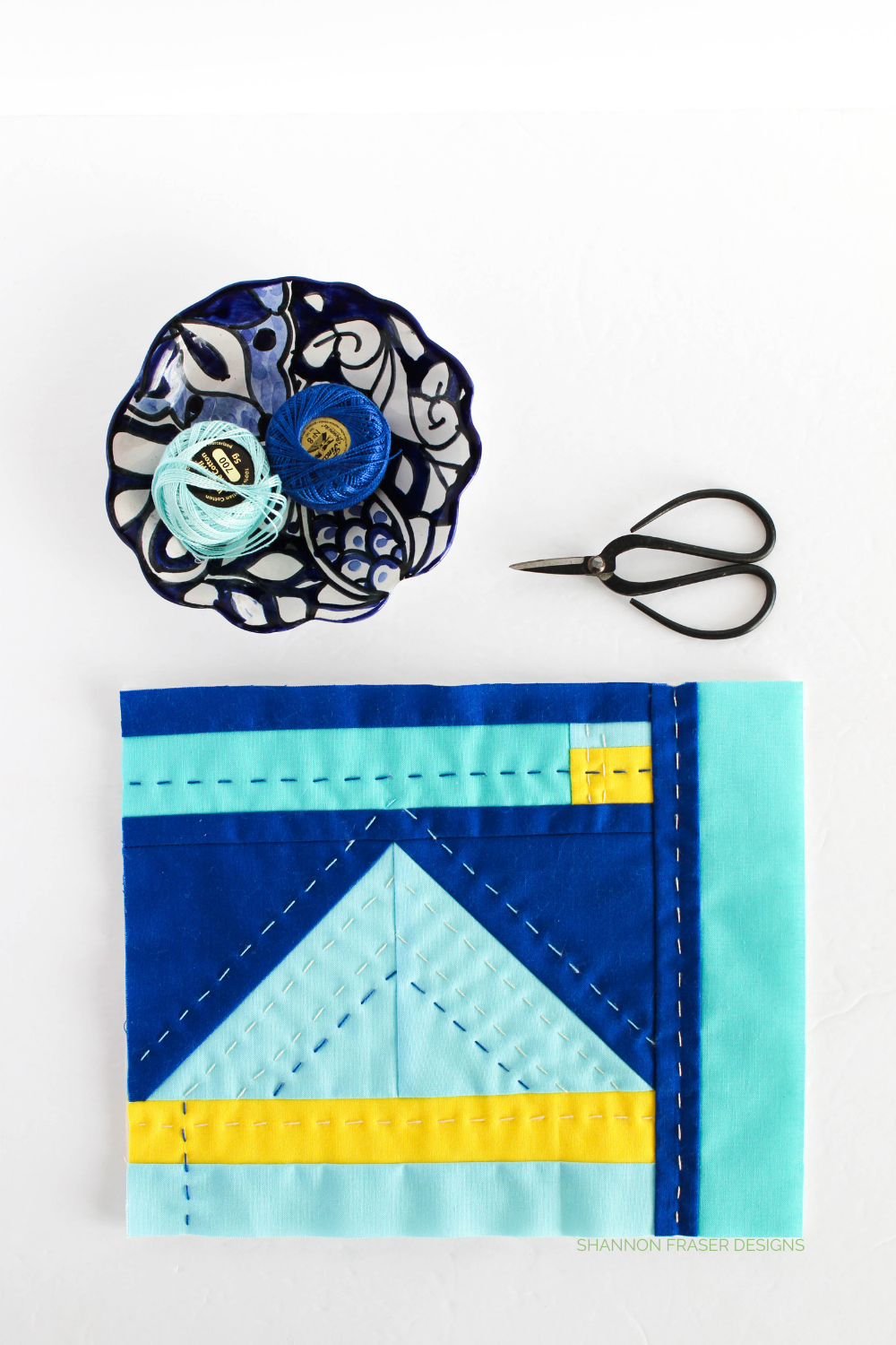 Modern mini improv quilt featuring shades of blue Kona Cotton with a pop of yellow. Hand quilted for added texture and dimension | Shannon Fraser Designs #artquilt #miniquilt