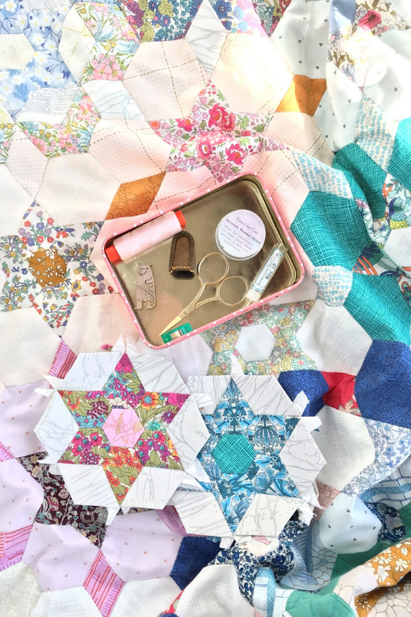Open tin featuring EPP notions on top of an English Paper Pieced star quilt | What's In your sewing bag?