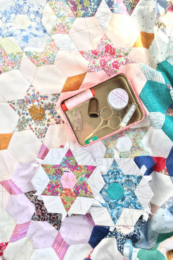 Metal tin featuring Ange's favourite English Paper Piecing notions sitting on top of her EPP quilt | What's in your sewing bag A Little Patchwork? | Shannon Fraser Designs #epp