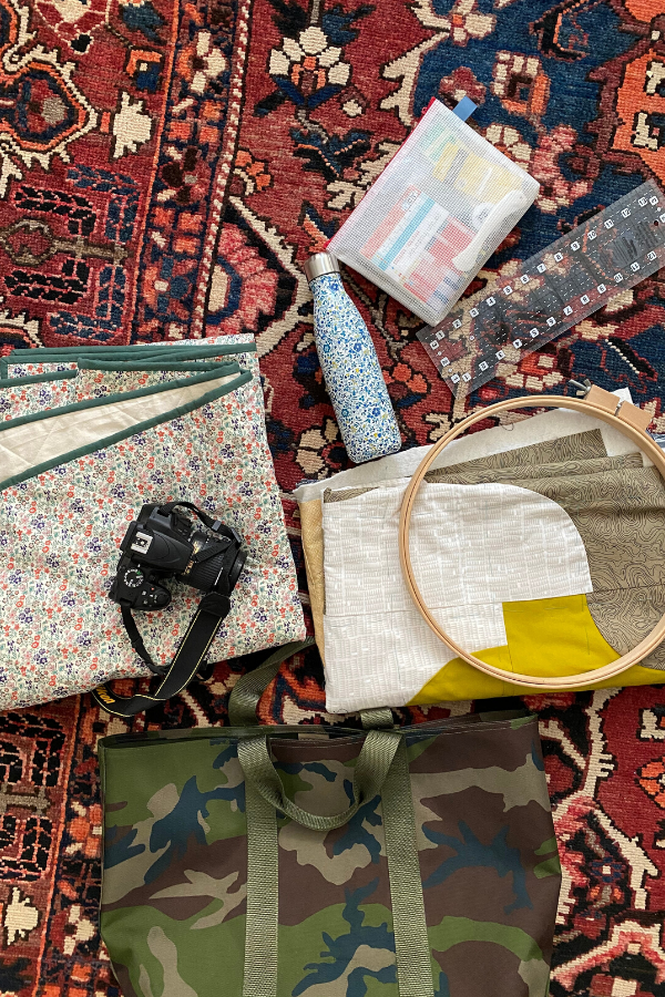 Camo LL Bean tote, camera, quilt folded up, Swell water bottle and quilting notions and tools
