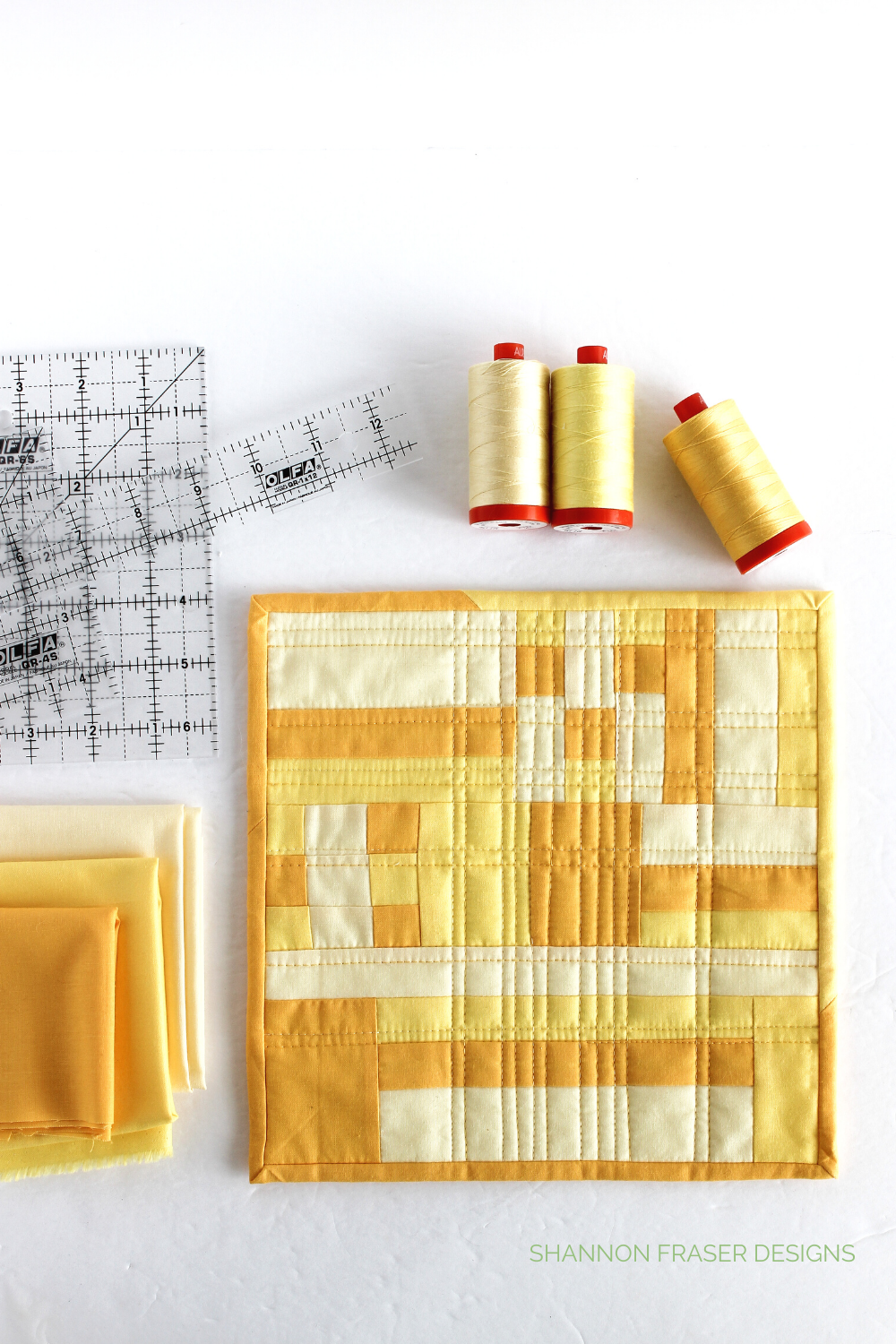 Sunshine on a Saturday morning mini quilt surrounded by the tools and materials used to create her: Olfa frosted rulers, Aurifil Thread 50wt yellow spools + Cotton Couture yellow Fat Quarter solids | Shannon Fraser Designs #artquilts