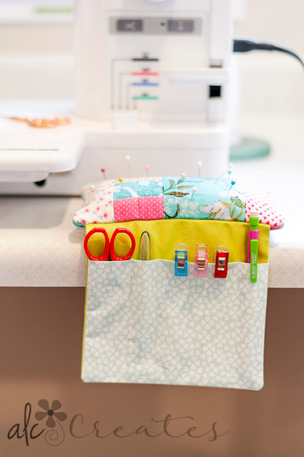 Sit 'n Sew pincushion hanging on Angela's sewing table in front of her Janome sewing machine | Sit 'n Sew Pincushion Pattern | Shannon Fraser Designs