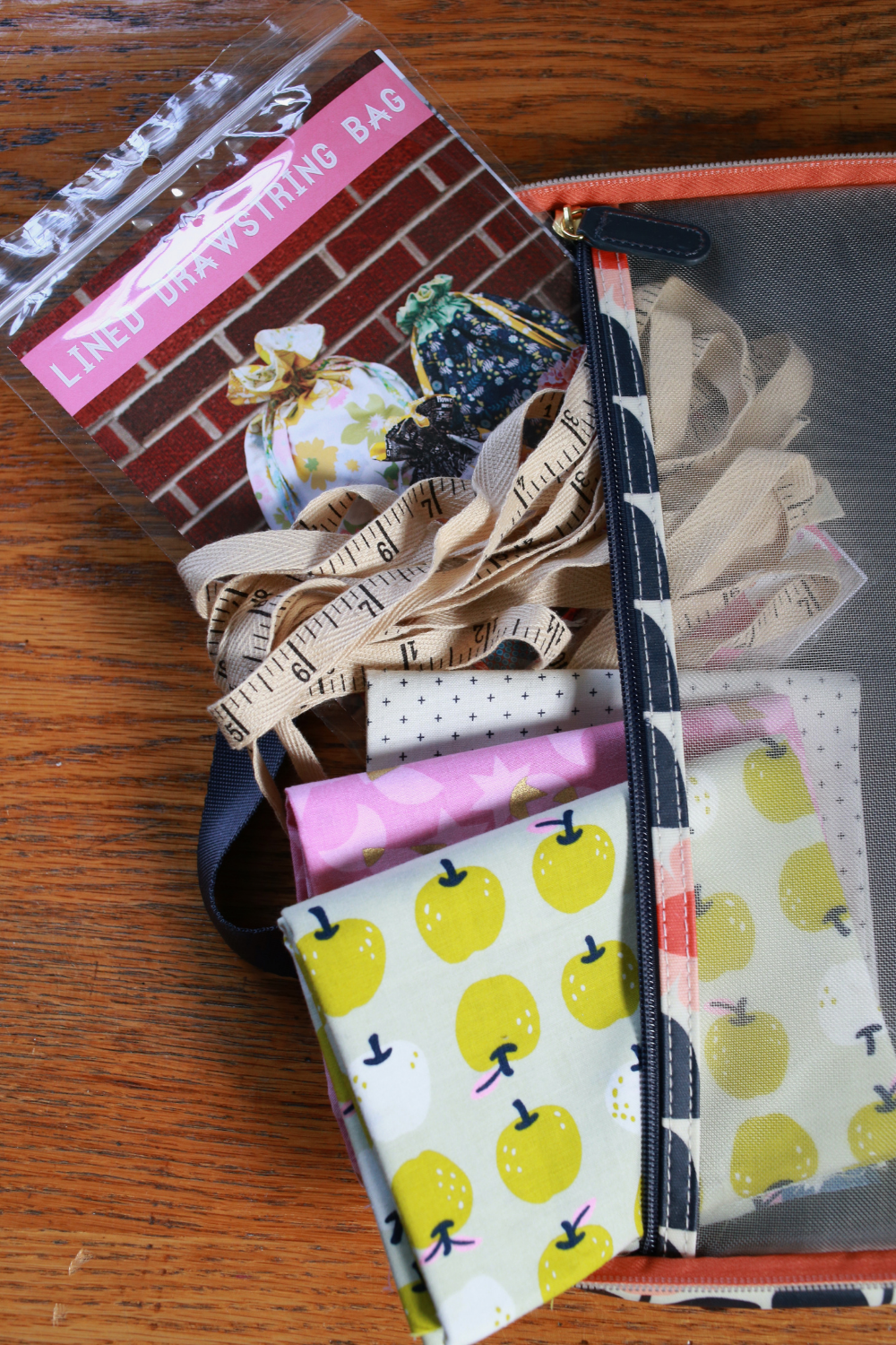 Pattern and fat quarters being tucked inside Jeni's travel sewing bag | What's in Your Sewing Bag In Color Order? | Shannon Fraser Designs' series #sewingpattern