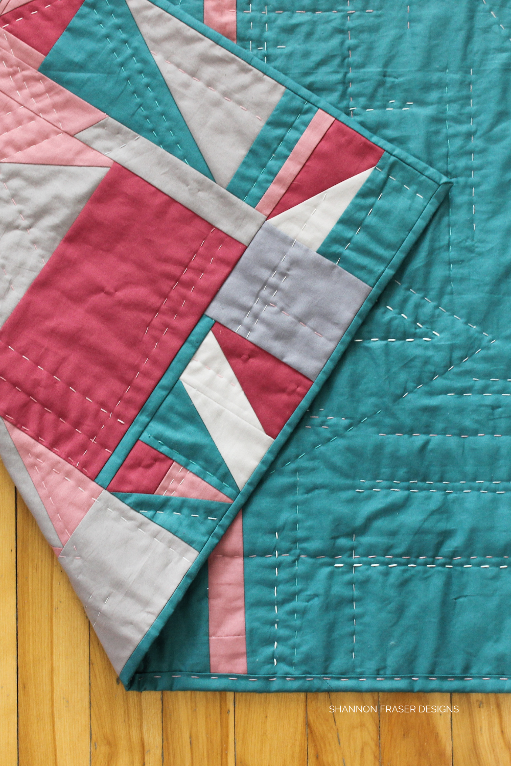Back of the Which Way Up quilt with the front flipped up - shows off the big stitch hand quilted using 4 different thread weights for maximum texture | Shannon Fraser Designs #improvquilt