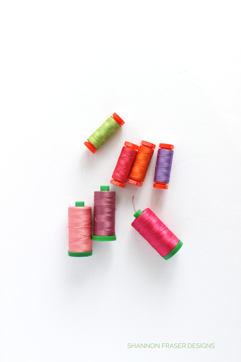 Small and large spools of Aurifil Thread in: green, red, purple, fuchsia, pink and mauve | Why I Love Aurifil Thread | Shannon Fraser Designs #thread