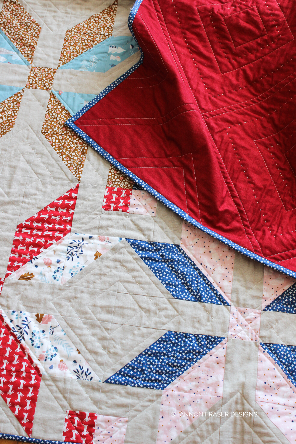 Winter Star lap quilt in blue, pink, red, beige and linen featuring machine and hand quilting details on this holiday version | Fat quarter friendly modern quilt pattern | Shannon Fraser Designs #handquilted