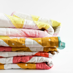 Pretty stack of bright colorful quilts featuring. Make your own today with the easy Pink Lemonade quilt pattern. #modernquilting #konacotton #quiltpattern