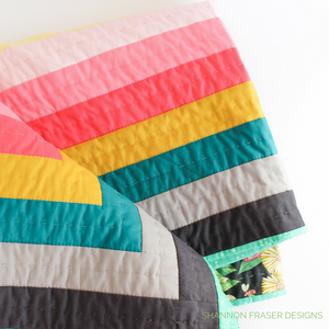 Rainbow quilt featuring modern log cabin quilt design using the Reveberance Quilt Pattern designed by Shannon Fraser Designs