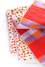 Load image into Gallery viewer, Big stitch binding detail plus the apples print by Heather Ross on the back of the Shattered Star quilt featuring Ruby & Bee solids in red, purple, orange, pink and lilac. Shannon Fraser Designs #modernquilt
