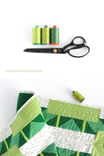 Load image into Gallery viewer, Green ombre large Aurifil thread spools with black tailor's shears and the Green ombre  Shattered Star quilted table runner | modern quilt pattern by Shannon Fraser Designs #quilting