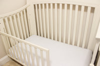 Crib with white crib sheet with navy blue polka dots.
