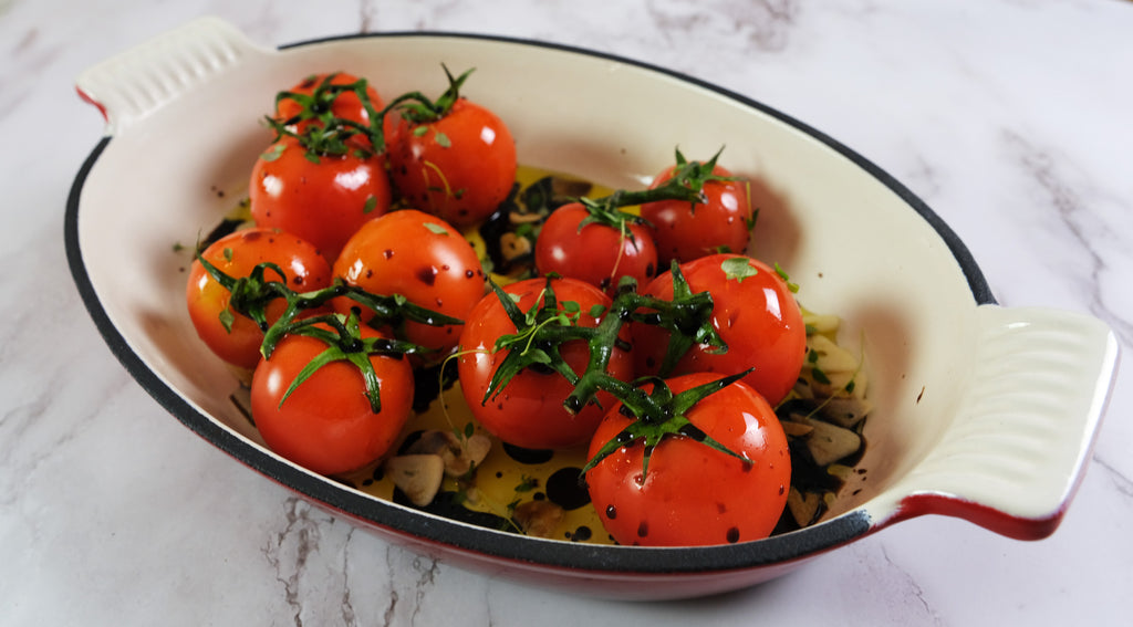 Roasted tomatoes in an emameled cast iron roasting pan