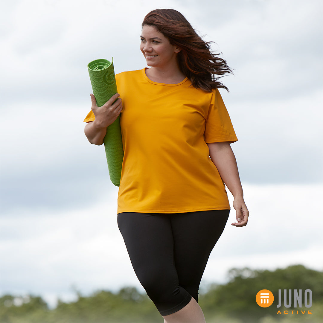 Woman wearing JunoActive plus size women's clothing holding a yoga mat in her arms.