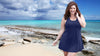 Woman at beach wearing JunoActive plus size swimwear AquaSport™ X Back Swim Dress pool friendly fabric