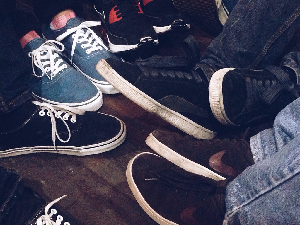 Close-up of a group of friends wearing a variety of sneakers.