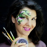Headshot of Olga Murasev the founder of the international face painting school. She is holding face paint and brushes