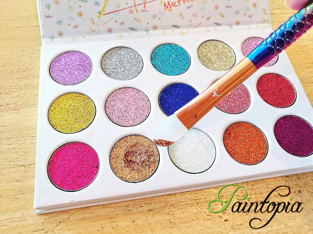 A cruelty free glitter eyeshadow palette containing pressed glitters in an assortment of shades including pinks, blues and purples.