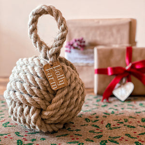 Country cottage inspired natural rope door stop, hand laid natural fibre flax hemp rope made in the UK crafted into a monkey fist knot doorstop with a personalised tag, inspired by coastal, nautical and country cottage interiors