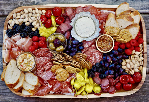 Charcuterie board with meats, cheeses, crackers, berries, and spreads