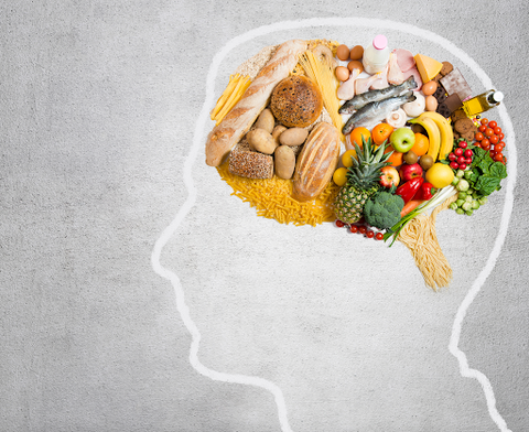Outline of human head with grains, vegetables, and other food where the brain would be