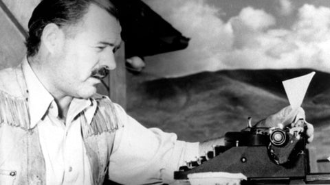 Memoirist Ernest Hemingway at his typewriter writing