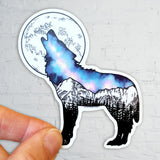 Wolf howling at a full moon with Galaxy inside and Maroon Bells mountain range in Aspen. Sticker