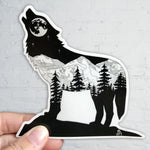 Wolf howling with full moon and mountain range inside silhouette