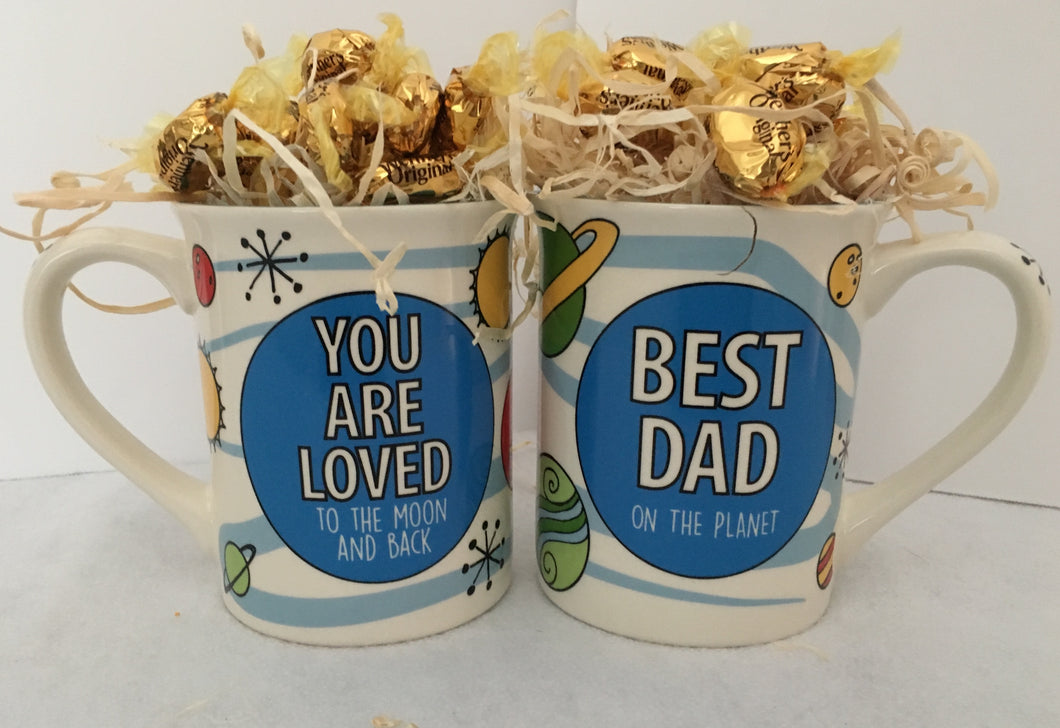 You Are Loved to the Moon and Back...Best Dad! This mug is decorated on the front and back. It is filled with candy and can also be added to another container and customized. It will be wrapped in a cello with a coordinating ribbon. We usually fill with overflowing chocolates unless you specify biscotti, hot cocoa, tea, or another choice