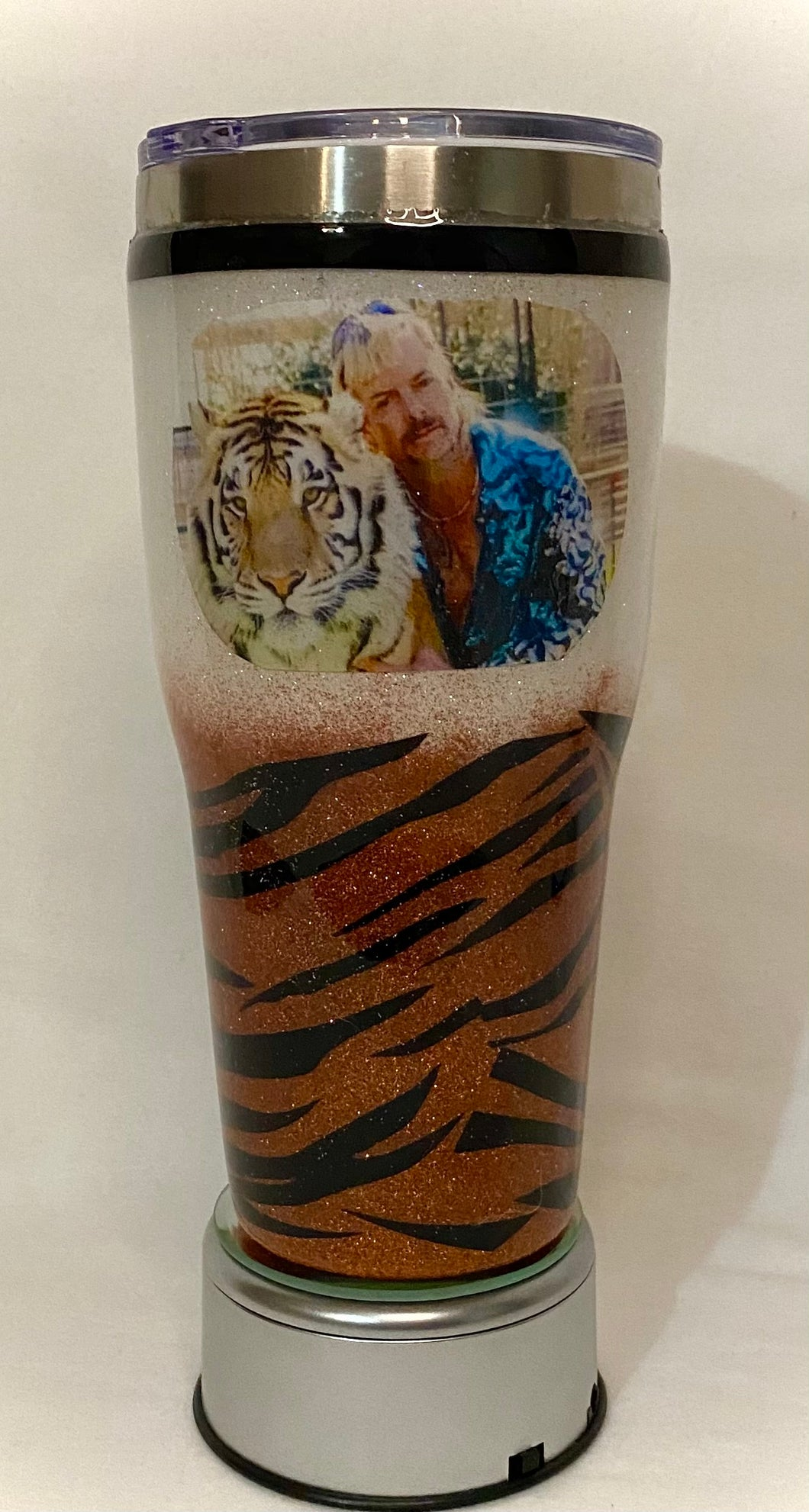 This Tiger King cup is a custom order for a customer. This cup is a 30-ounce stainless steel tumbler that can hold liquids hot/cold for hours. It is decorated in glitter, vinyl, a photo, and FDA food-approved epoxy. It comes with a lid. We can custom design these tumblers any way you like. We can add monograms, names, sayings, etc. We can design by color, size, and your preference for personalization. Call us or email us at 704.526.7407 or email us at perfectselectioncreativegifts@gmail.com and let us desig
