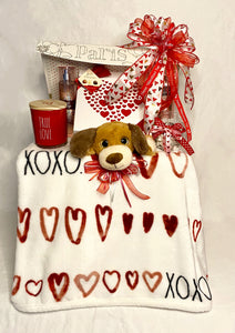 """Hugs & Kisses"" xoxoxo is the perfect Valentine's Day Gift for that Special Someone! This beautiful flip-top box is filled with lots of hugs and kisses. Your Valentine will feel the LOVE!  Included is:  Super-soft Throw with X's & O's, and Hearts A Box of Chocolates Bath and Body ""A Thousand Wishes"" Lotion Bath and Body ""A Thousand Wishes"" Body Spray A Wonderful Full-Size Candle A Hot Cocoa Bomb  And this Adorable Stuffed Puppy"