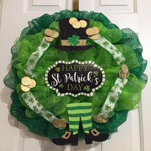 "Happy Saint Patrick's Day Wreath is a two-toned green mesh wreath approximately 24"" in diameter and decorated with gold coins, ribbon, and wooden pieces that say ""Happy St. Patrick's Day."" These can be ordered now and can be delivered within a week or two. We can add additional ribbons to wreaths and reserve the right to substitute signs. We can ship this nationwide. The back of the wreath is covered with felt to protect wall or doors."