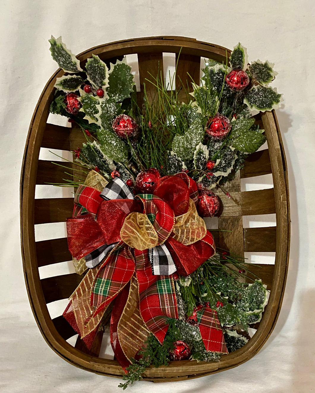 Holiday Tobacco Basket is a beautiful handmade wall decor decorated with holly, Christmas picks, berries, red bells, and snow. It measures 19
