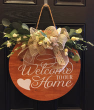 "Load image into Gallery viewer, ""Welcome to Our Home"" is a beautiful handmade door or wall decor made of real pine wood. This piece has been sanded and stained to bring out the true beauty of the wood. It has a white permanent vinyl quote, silk flowers with a matching handmade bow. The decorative three-strand hanging rope has guides to prevent sliding and cork protectors are on the back of this decor to protect your wall or door."