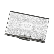 Load image into Gallery viewer, Feminine shiny silver metal business card holder engraved in a center oval with a monogram. Outside the oval shape is a paisley and scroll design embossed throughout.