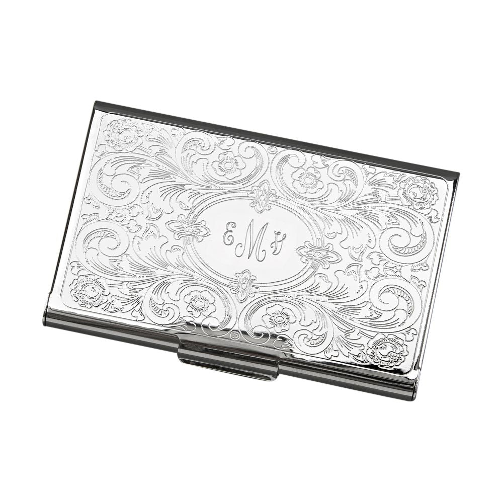 Feminine shiny silver metal business card holder engraved in a center oval with a monogram. Outside the oval shape is a paisley and scroll design embossed throughout.
