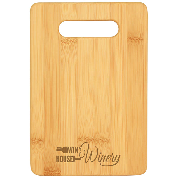 Small rectangle cutting board with cut out handle featuring a winery's custom logo engraved at the bottom center.